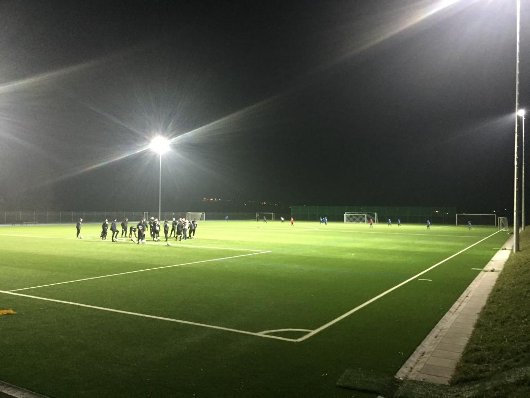 Sportplatz im Flutlicht mit Trainingsgruppen